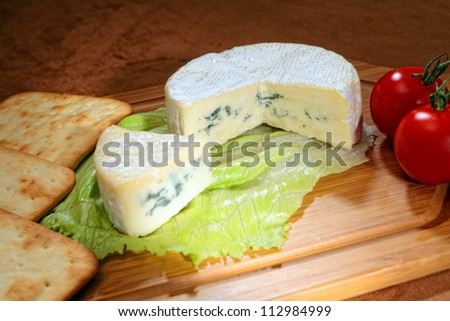 A wheel of blue-veined camembert with cherry tomatoes and cream cracker biscuits