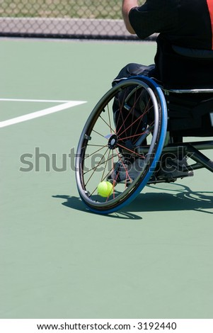 A wheelchair bound athlete on the tennis court - showing the angle of the wheel and the tennis ball being held in