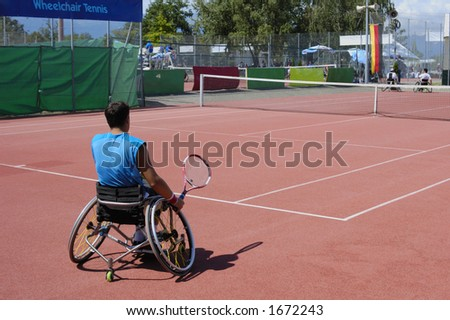 A wheelchair tennis player during a tennis championship match, preparing to take a shot.