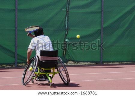 A wheelchair tennis player during a tennis championship match, taking a shot. - stock photo