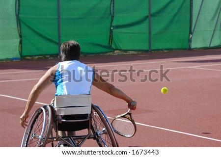 A wheelchair tennis player during a tennis championship match, taking a shot.