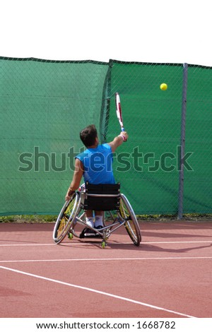 A wheelchair tennis player during a tennis championship match, taking a shot. Space for text above the fence.