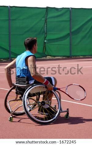 A wheelchair tennis player during a tennis championship match, waiting to take a shot.