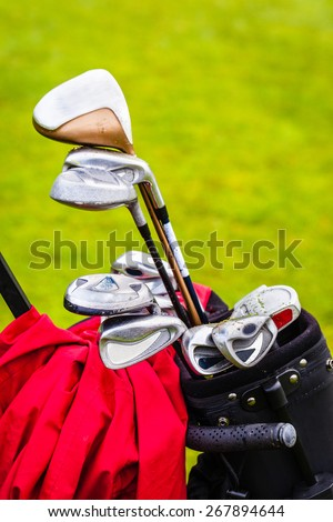 a wheeled golf bag full of golf clubs of a vibrant golf course