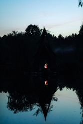 A whimsical house in the middle of the lake in the evening with a couple in love inside. Romantic date.