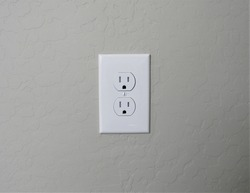 A white American electrical outlet on a stucco wall in southwest America