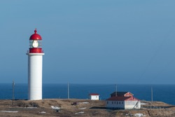 A white and red cylinder shaped concrete lighthouse with a large green glass light in the top red tower section on a cliff overlooking the blue sky and ocean with small outcrop and storage buildings.