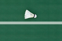 A white badminton feather shuttlecock at a corner on a badminton court.