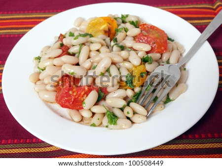 A white bean and grilled tomato salad with a  fork.