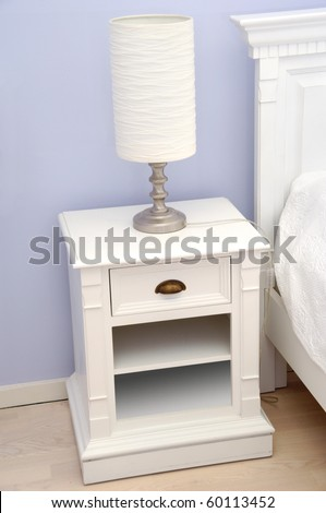 A white bedside table with a white lamp