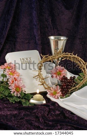 A white bible, chalice, flowers, crown of thorns, candle, pink daisies and grapes are displayed over a purple back drop with room for copy. - stock photo