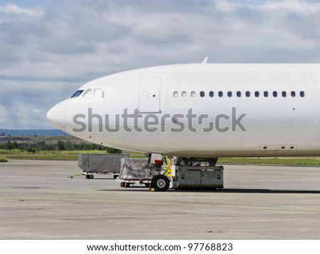 A white, big airplane waiting for next flight in a small airport