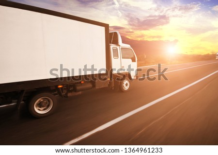 A white big box truck with space for text driving fast on the countryside road with trees and bushes against a night sky with sunset