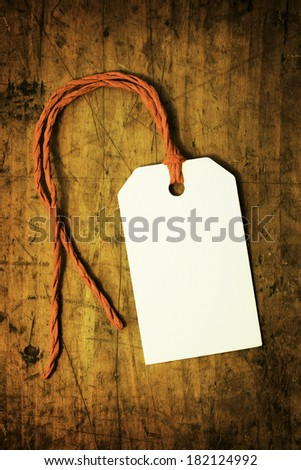 A white blank paper tag on a old wooden desk