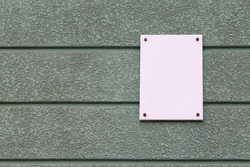 A white blank plate on the house attached with four rivets, with space for text, lettering or image