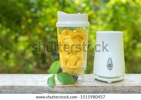 A white blender with pineapple slices inside stands on a wooden table against the summer foliage. Smoothie maker mixer with pieces of fruit ingredients. Healthy drink and lifestyle. Detox and diet. #1511980457