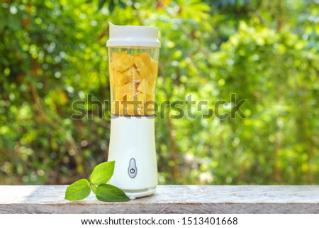 A white blender with pineapple slices inside stands on a wooden table against the summer foliage. Smoothie maker mixer with pieces of fruit ingredients. Healthy drink and lifestyle. Detox and diet. #1513401668