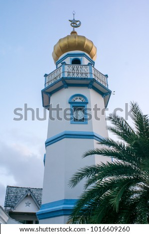 A white blue Minaret with golden onion shaped crown and silver star and crescent on top, Minaret is the tower built close to the mosque for Adhan (Calling for prayer in Islam) #1016609260