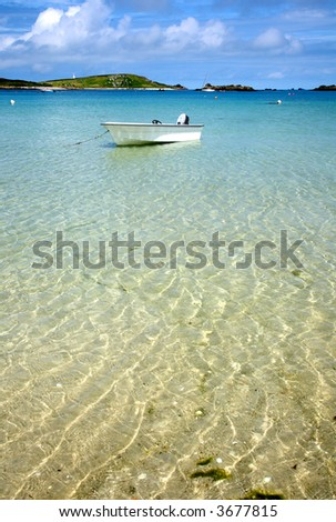 A white boat floating on clear sea, Isles of Scilly, Cornwall.