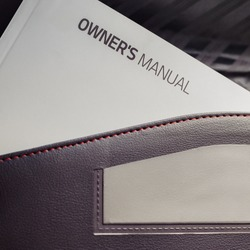 A white book placed in all new vehicles called an owner's manual usually placed in a black leather pouch located inside the glove compartment.