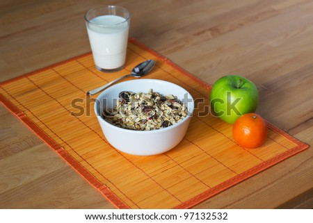 a white bowl filled with cereal, next to a glass of milk and an apple and a tangerine
