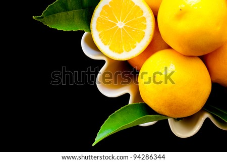 A white bowl full of yellow lemons with green leaves, isolated against black, with one cut in half. Close up, top view, looking down.