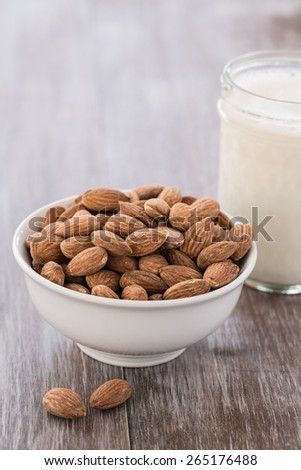 A white bowl of almonds and a glass of almond milk on wood background