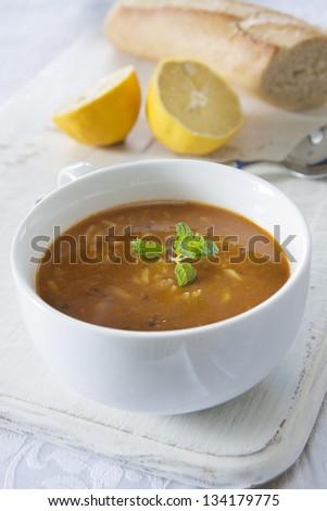 A white bowl of Mulligatawny soup garnished with mint leaf