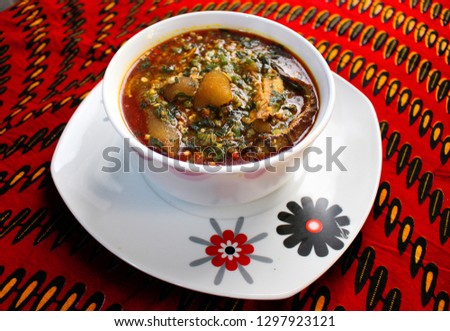 A white bowl of okra soup with cow skin meat (Nigerian kpomo) and dried fish served on a colorful red table cloth