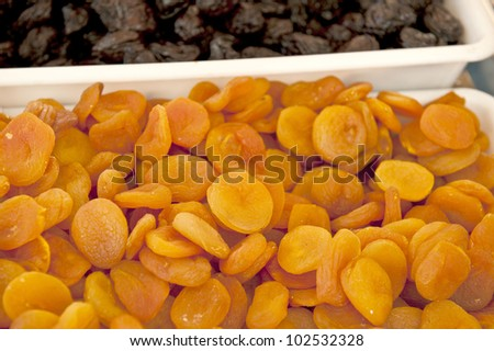 A white box of dried, bright orange apricots next to black raisins.