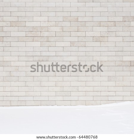 A white brick wall and a ground covered with snow. May use as a background.