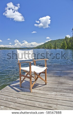 A white canvas chair on the dock of a beautiful lake with blue sky and clouds