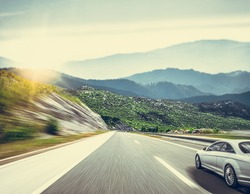 A white car on the road against the backdrop of a beautiful countryside landscape.