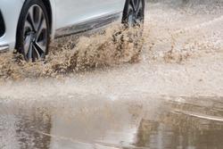 a white car speeding through the sewage road splashing yellow water splash