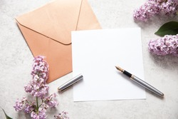 A white card and golden envelope with an oldschool fountain ink pen and white keyboard and lilac flowers. Text space, top view.