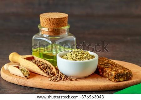 A white ceramic bowl full of shelled hemp, seeds and hemp oil
