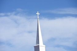 A white church steeple on a blue sky with white clounds