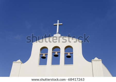 A white church with a cross and three bells against a blue sky.