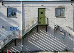 A white cinder block building with metal stairs to a green door, blocked windows,  and a graffiti on the wall.