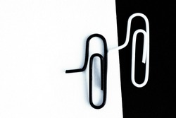 A white-clipped paperclip sits on a black surface and another black paperclip sits on a white surface - black and white concept with paperclips - stark contrasts and differences as background