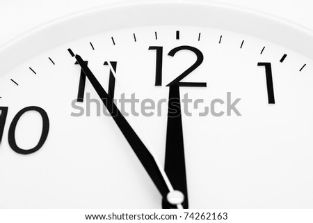 a white clock - five minutes to twelve, closeup