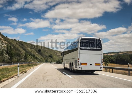 A white coach, or long haul bus for tourists drives through the open roads of Spain, Europe on a summer day. There are white clouds against a blue sky and countryside.