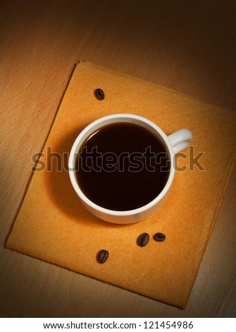 A white coffee cup on a yellow napkin, top view
