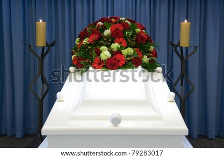 A white coffin in a mortuary with a flower-arrangement