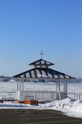 A white colored wooden gazebo with a black roof and snow on the ground in winter, view of the St. Lawrence river with white ice and a blue sky