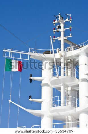 A white cruise ship tower flying the Italian flag against a blue sky