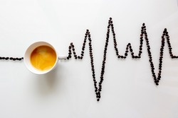 A white cup full of black coffee between coffee beans forming a heartbeat curve on a white clean background.