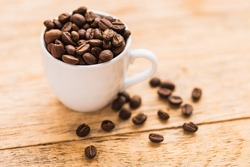 A white cup full of brown coffee beans