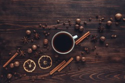 A white Cup of coffee and spices on a wooden table. The concept of a hot drink. Coffee shop, espresso, spices, top view. Copy space