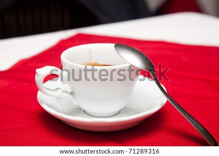 A white cup of coffee on a red table cloth